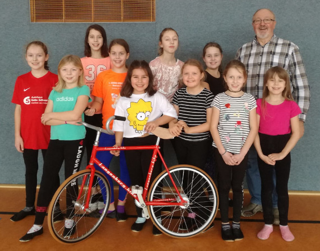 Die Mädchen freuen sich mit dem 1. Vorsitzenden über das neue Kunstrad
